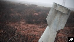 FILE - In this Sunday Jan. 6, 2013 photo, an unexploded bomb lies half-buried in the ground in Taftanaz, Syria.