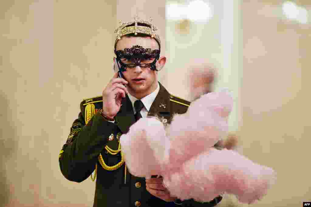 A military cadet holds cotton candy while on his mobile phone during the Big New Year Ball at the Bolshoi Opera and Ballet Theatre in Minsk, Belarus, Jan. 13, 2019.
