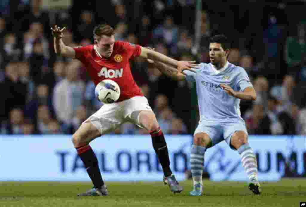 Manchester City's Sergio Aguero, right, fights for the ball against Manchester United's Phil Jones during their English Premier League soccer match at The Etihad Stadium, Manchester, England, Monday, April 30, 2012. (AP Photo/Jon Super)