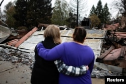 FILE - Neighbors comfort each other after the Camp Fire in Paradise, California, U.S. November 22, 2018. (REUTERS/Elijah Nouvelage)