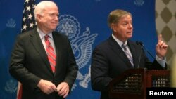 U.S. Senator Lindsey Graham (R) speaks as compatriot Senator John McCain looks on during a news conference in Cairo, August 6, 2013.