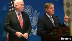 U.S. Senator Lindsey Graham (R) speaks as Senator John McCain looks on during a news conference in Cairo, August 6, 2013.