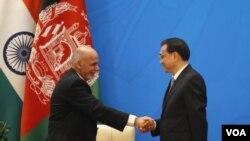 ປະທານາມິບໍດີອັຟການິສຖານ ທ່ານ Ashraf Ghani (ຊ້າຍ) ສຳພັດມືກັບນາຍົກລັດຖະມົນຕີຈີນ ທ່ານ Le Kequiang.