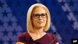 FILE - U.S. Rep. Kyrsten Sinema, D-Ariz., goes over the rules in a television studio prior to a televised debate with U.S. Rep. Martha McSally, R-Ariz., in Phoenix, Oct. 15, 2018.