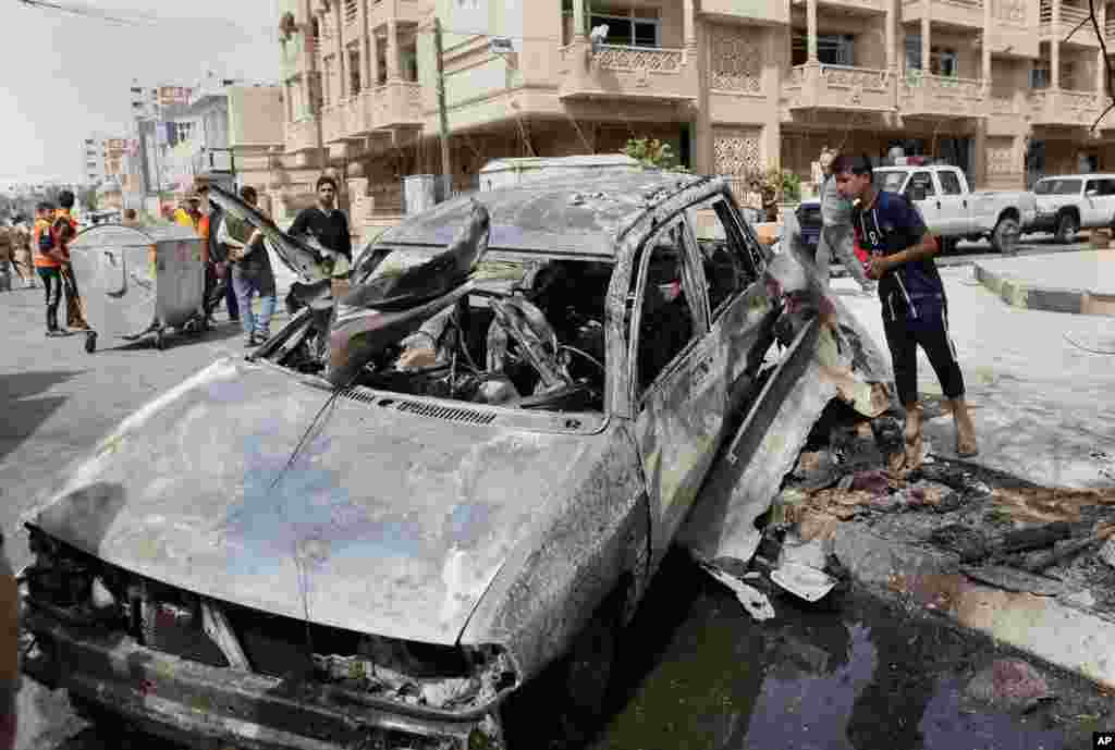 People inspect a car destroyed in a car bomb attack close to one of the main gates to the heavily-fortified Green Zone in Baghdad, Iraq, March 19, 2013.