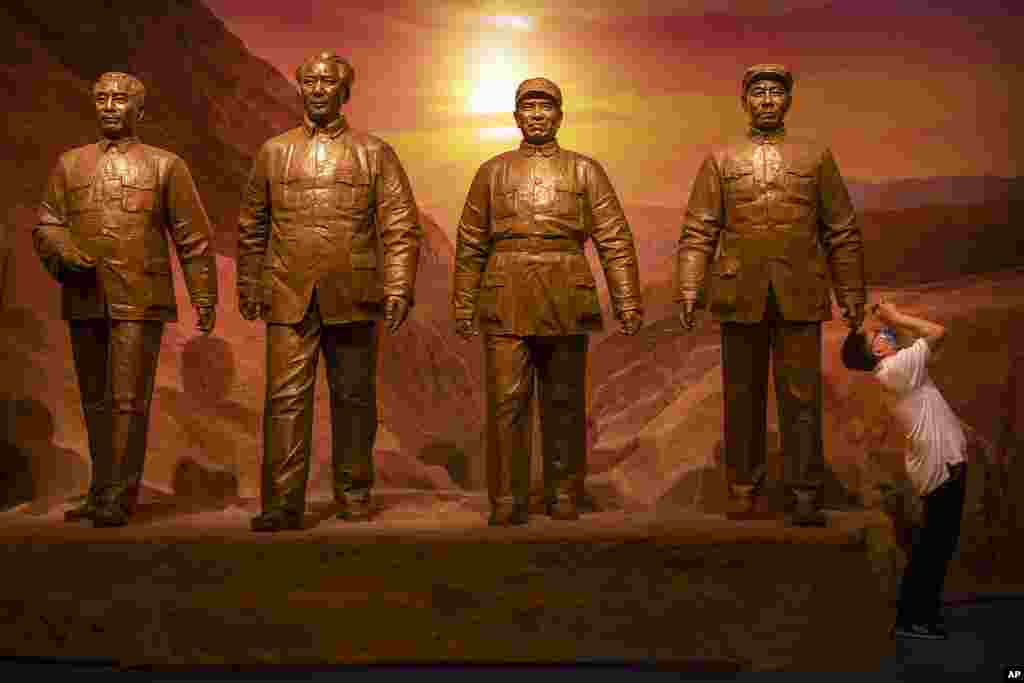 A visitor takes a photo of an exhibit near a statue of Chinese leader Mao Zedong, 2nd from left, and other Communist Party figures at the newly-completed Museum of the Communist Party of China in Beijing.