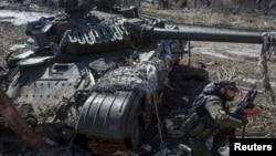 16일 우크라이나 동부 도네츠크 외곽 스파르타크 지역에서 반군 병사가 손상된 정부군 탱크 앞에 앉아 있다.