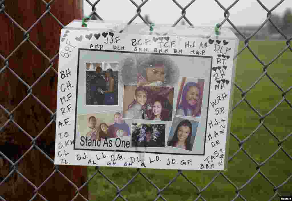 A memorial consisting of photos of the victims is seen outside of Marysville-Pilchuck High School the day after a school shooting in Marysville, Washington, Oct. 25, 2014.