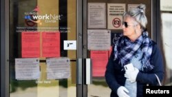 A woman looks to get information about job application in front of IDES (Illinois Department of Employment Security) WorkNet center in Arlington Heights, Ill., Thursday, April 9, 2020.