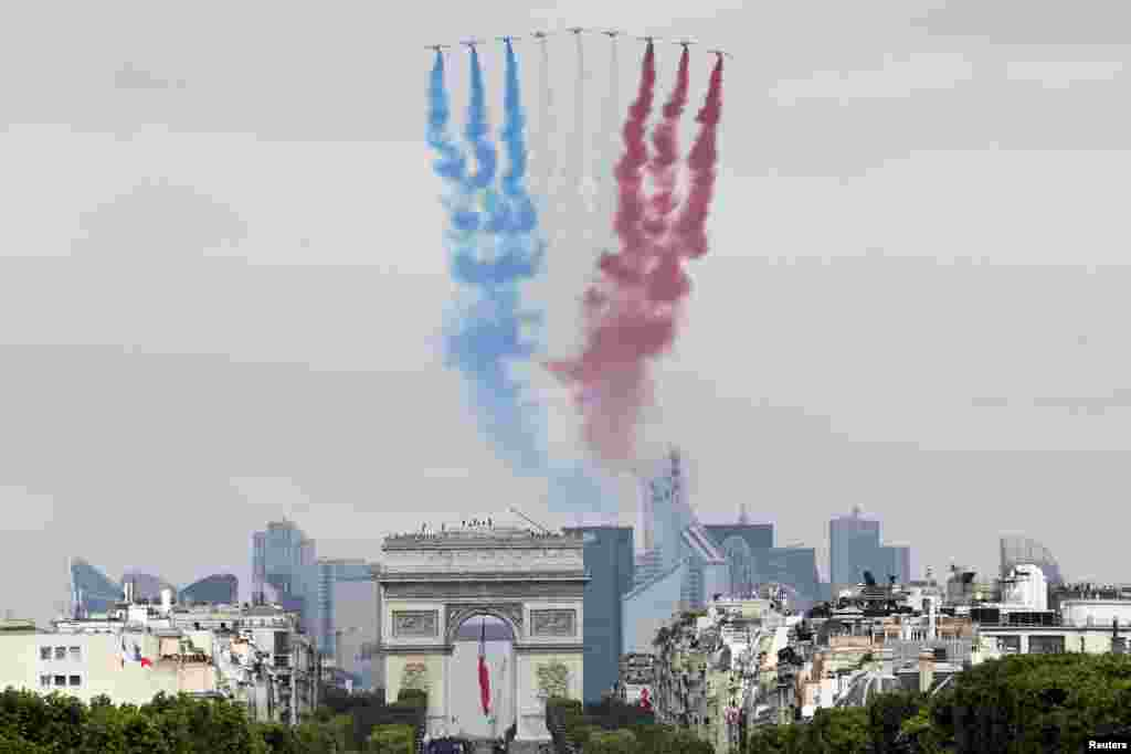 Nine alphajets from the French Air Force Patrouille de France release a trail of national colors as they fly above the Arc de Triomphe and the Champs-Elysees during the annual Bastille Day military parade in Paris, July 14, 2014.