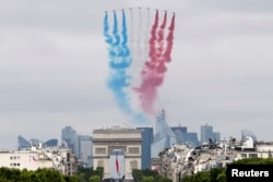 FILE - Nine alphajets from the French Air Force Patrouille de France release France's national colours trail as they fly above the Arc de Triomphe and the Champs-Elysees avenue during the traditional Bastille Day military parade in Paris, July 14, 2014.