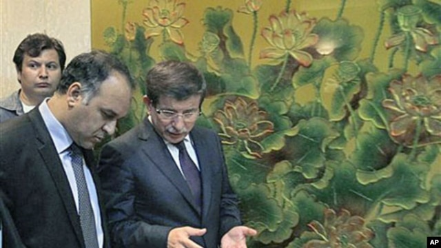 Turkish Foreign Minister Ahmet Davutoglu (R) speaks to Vice-Chairman of the Executive Board of the Libyan National Transitional Congress Ali al-Issawi (L) before a news conference after their meeting in the rebel-held Benghazi, Libya, July 3, 2011