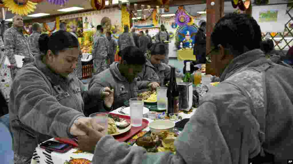 U.S. Army soldiers serving in the NATO-led peacekeeping mission in Kosovo pray before sharing a traditional Thanksgiving meal at the military base Camp Bondsteel, Nov. 27, 2014.