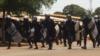 Des policiers essaient de stopper la marche qui se dirige evrs l'autoroute, lors d'une manifestation à Conakry, en Guinée, le 22 mars 2018. (VOA/Zakaria Camara)