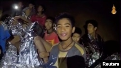 Boys from the soccer team trapped inside Tham Luang cave covered in hypothermia blankets react to the camera in Chiang Rai, Thailand, in this still image taken from a July 3, 2018 video by Thai Navy Seal. Thai Navy Seal/Handout via REUTERS