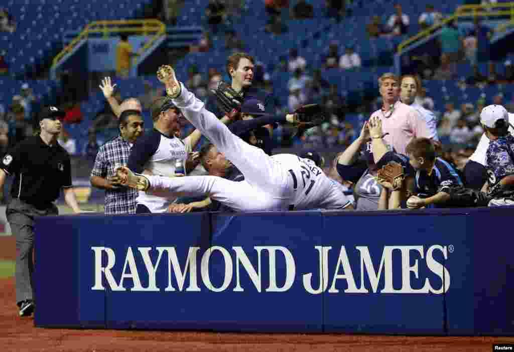 Cầu thủ bóng chày của đội Tampa Bay Rays, James Loney (21), ngã vào khán đài sau khi cố gắng chụp một quả bóng phạm lỗi trong trận đấu với đội Detroit Tigers tại Sân Tropicana Field ở thành phố St. Petersburg, bang Florida, Mỹ. (Hình: Kim Klement/USA TODAY Sports)