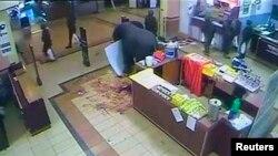 2013年10月19日路透社得到的闭路电视录像: 静止图像似乎显示士兵从柜台上拿走商品并携带购物塑料袋离开超市