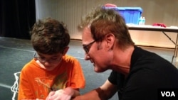 Magician Kevin Spencer teaches Liam Shannon a magic trick. (VOA/ J.Taboh)