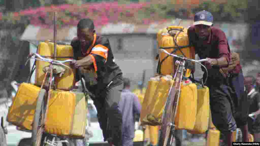 Des hommes poussent leurs vélos chargés des bidons d'eau du lac Kivu