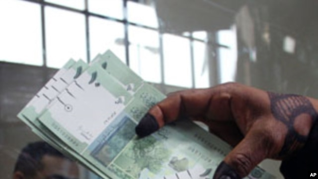 A woman displays Sudan's new currency at the central bank in Khartoum, Sudan. The Sudanese government began circulating a new edition of the Sudanese pound on Sunday as a precautionary measure following the loss of oil revenues resulting from South Sudan'