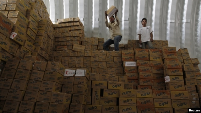 Two workers unload boxes of aid inside a warehouse at the Mrajeeb Al Fhood refugee camp for Syrian refugees, 20 kilometers east of the city of Zarqa, Jordan, April 29, 2013.