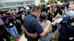 Chèf Polis vil Houston nan, Art Acevedo, avèk Charlene Davis, ki t ap bay akolad apre Madam Davis te fin priye pou kòmandan an nan okazyon ekspozisyon kò George Floyd nan Legliz Fontèn d Adorasyon nan Houston, lendi 8 jen 2020. (Foto: AP/Eric Gay).