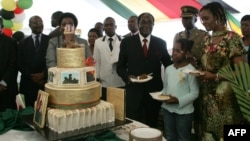 FILE: Zimbabwe President Robert Mugabe (4th R) and first lady Grace Mugabe (2nd R) stand with the presidents birthday cake among guests on the occasion of his 89th birthday celebrations held in his honour at the State House, the eve of his birthday, February 20.