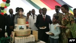 FILE: Zimbabwe President Robert Mugabe (4th R) and first lady Grace Mugabe (2nd R) stand with the presidents birthday cake among guests on the occasion of his 89th birthday celebrations held in his honour at the State House, the eve of his birthday, February 20