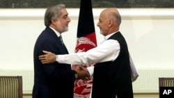 Afghanistan's presidential election candidates Abdullah Abdullah, left, and Ashraf Ghani Ahmadzai shake hands after signing a power-sharing deal at the presidential palace in Kabul, Afghanistan, Sept. 21, 2014