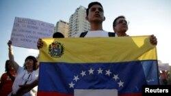 """ຜູ້ສະໜັບສະໜຸນຝ່າຍຄ້ານ ຖືທຸງເວເນຊູເອລາ ແລະ ປ້າຍທີ່ຂຽນວ່າ """"ບໍ່ໃຫ້ມີຜະເດັດການຕໍ່ໄປອີກແລ້ວ"""" ໃນຕອນທີ່ເຂົ້າຮ່ວມການຊຸມນຸມ ປະທ້ວງ ຕ້ານລັດຖະບານ ຂອງທ່ານ Nicolas Maduro ໃນນະຄອນຫລວງ Caracas, ວັນທີ 30 ມີນາ 2017."""