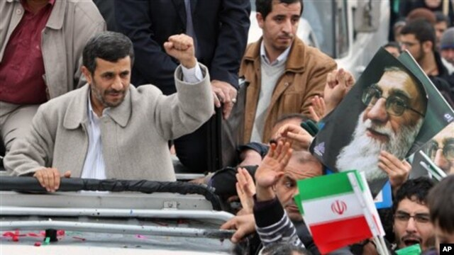 Iranian President Mahmoud Ahmadinejad, clenches his fist from his car, as he attends a rally marking the 32nd anniversary of 1979 Islamic Revolution, Feb 11, 2011