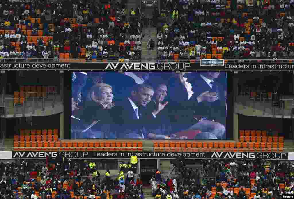 U.S. President Barack Obama (C) and his wife Michelle are seen on a big screen at the First National Bank (FNB) Stadium, also known as Soccer City, during the national memorial service for former South African President Nelson Mandela in Johannesburg Dece