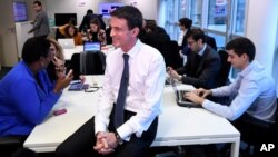Former French Prime Minister Manuel Valls, now the candidate for the socialist party primary election, smiles during the inauguration of his campaign headquarters, Dec. 14, 2016, in Paris. French officials are working to secure the election from cyberattacks.