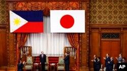 阿基諾(左二)在日本國會發表演講前受到國會議員拍掌歡迎