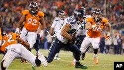 Pemain Seattle Seahawks, Doug Baldwin (89), melewati para pemain Denver Broncos dalam final Super Bowl 2014 (2/2). (AP/Evan Vucci)