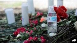 Sebotol air, bunga, lilin, dan boneka binatang ditempatkan di lapangan parkir toko Walmart dekat lokasi dimana pihak berwenang menemukan truk yang dijejali imigran di San Antonio, Texas (foto: AP Photo/Eric Gay)