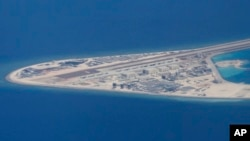 FILE - In this April 21, 2017, photo, an airstrip and buildings on China's man-made Subi Reef in the Spratly chain of islands in the South China Sea are seen from a Philippine Air Force C-130.