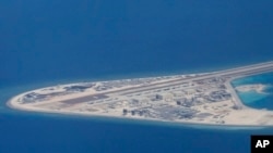 In this April 21, 2017, photo, an airstrip and buildings on China's man-made Subi Reef in the Spratly chain of islands in the South China Sea are seen from a Philippine Air Force C-130.