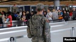 Un militaire veillant sur la ligne d'embarquement à l'aéroport John F. Kennedy international de New York, 29 juin, 2016.