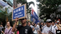 FILE - Protesters hold placards and wave colonial-era flags at an annual pro-democracy rally in Hong Kong, July 1, 2016. As the territory prepares for legislative elections, a new pledge of loyalty to China candidates are required to sign is creating friction.