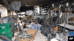 In this photo released by the Syrian official news agency, SANA, a damaged equipment storage room of the Ikhbariya TV station is seen after it was attacked by gunmen in the town of Drousha, south of Damascus, June 27, 2012.