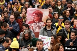 FILE - People protest after former president Carles Puigdemont was detained in Germany, during a demonstration held by pro-independence associations in Barcelona, Spain, March 25, 2018.