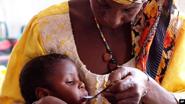 Mother feeding her severely malnourished daughter at center in Niger run by CONCERN and supported by WFP in October 2010.