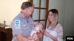 Mechanic and volunteer EMT Jeff Olson visits the baby whose life he saved last September. Mother Karen Garrison looks on in Spokane, Washington. (VOA/T. Banse)