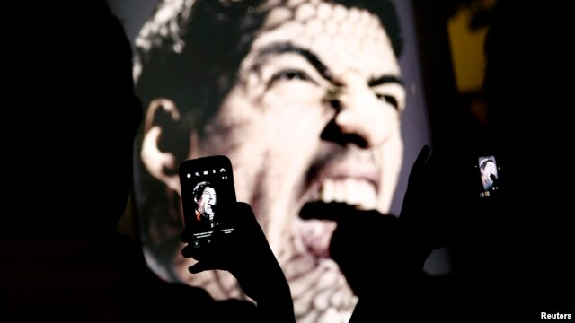 People use mobile devices to take pictures of an advertising placard showing Uruguay's striker Luis Suarez flashing his teeth, Copacabana beach, Rio de Janeiro, June 26, 2014.