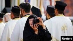 Seorang biarawati mengambil gambar di tengah umat yang merayakan 1.700 tahun Fatwa Milan, atau fatwa toleransi umat Kristen, di kota Nis, Serbia (6/10). (Reuters/Marko Djurica)