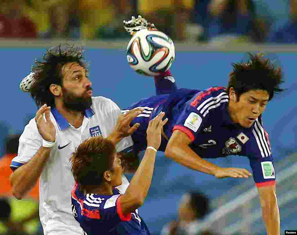 Japan's Atsuto Uchida is fouled by Greece's Giorgios Samaras during their 2014 World Cup Group C soccer match at the Dunas arena in Natal, June 19, 2014.