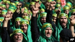 "Lebanese Shi'ite supporters of the Iranian-backed Hezbollah group, shout slogans as they march marking the Ashoura holiday, in a southern suburb of Beirut, Lebanon, Oct. 12, 2016. Hezbollah – known as ""the Party of God"" – is considered a terrorist organization by the U.S. and European allies, and follows a Shi'ite ideology that calls for the destruction of Israel."