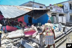 A woman stands in front of a destroyed home in the aftermath of an earthquake in Les Cayes, Haiti, Aug. 14, 2021.