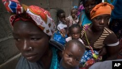 Displaced women with their children wait for assistance at a building used by refugees as shelter in Pemba, Mozambique, after they fled attacks in Palma in Northern Mozambique, April 19, 2021.